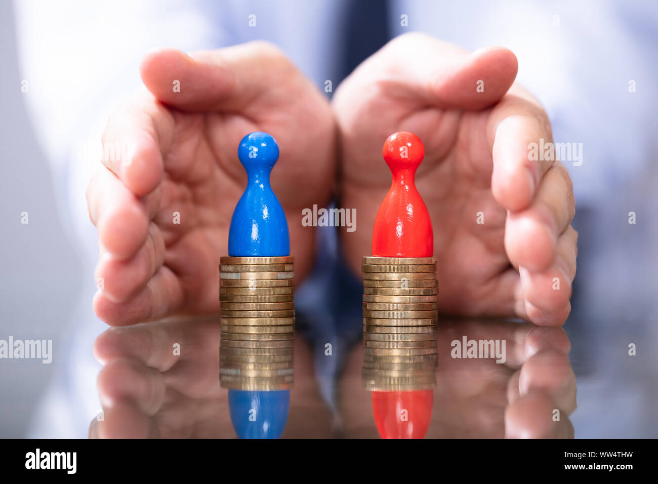 Man Protecting To Coin Stacks. Equal Pay For Men And Women Stock Photo