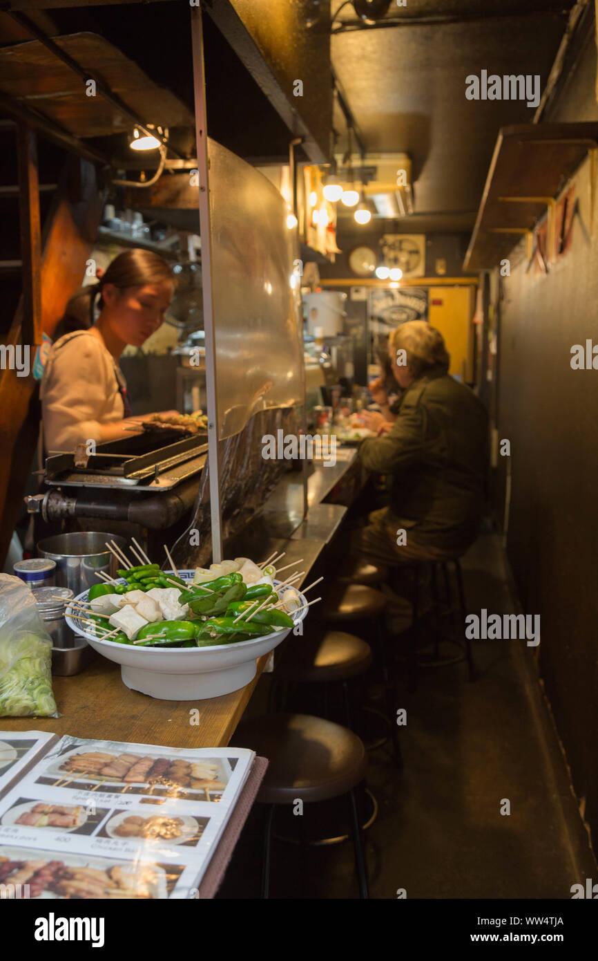 Shinjuku, Tokyo, Japan. In recent days, Izakaya became increasingly popular among foreign visitors, with an English menu, owner prepares food for them. Stock Photo