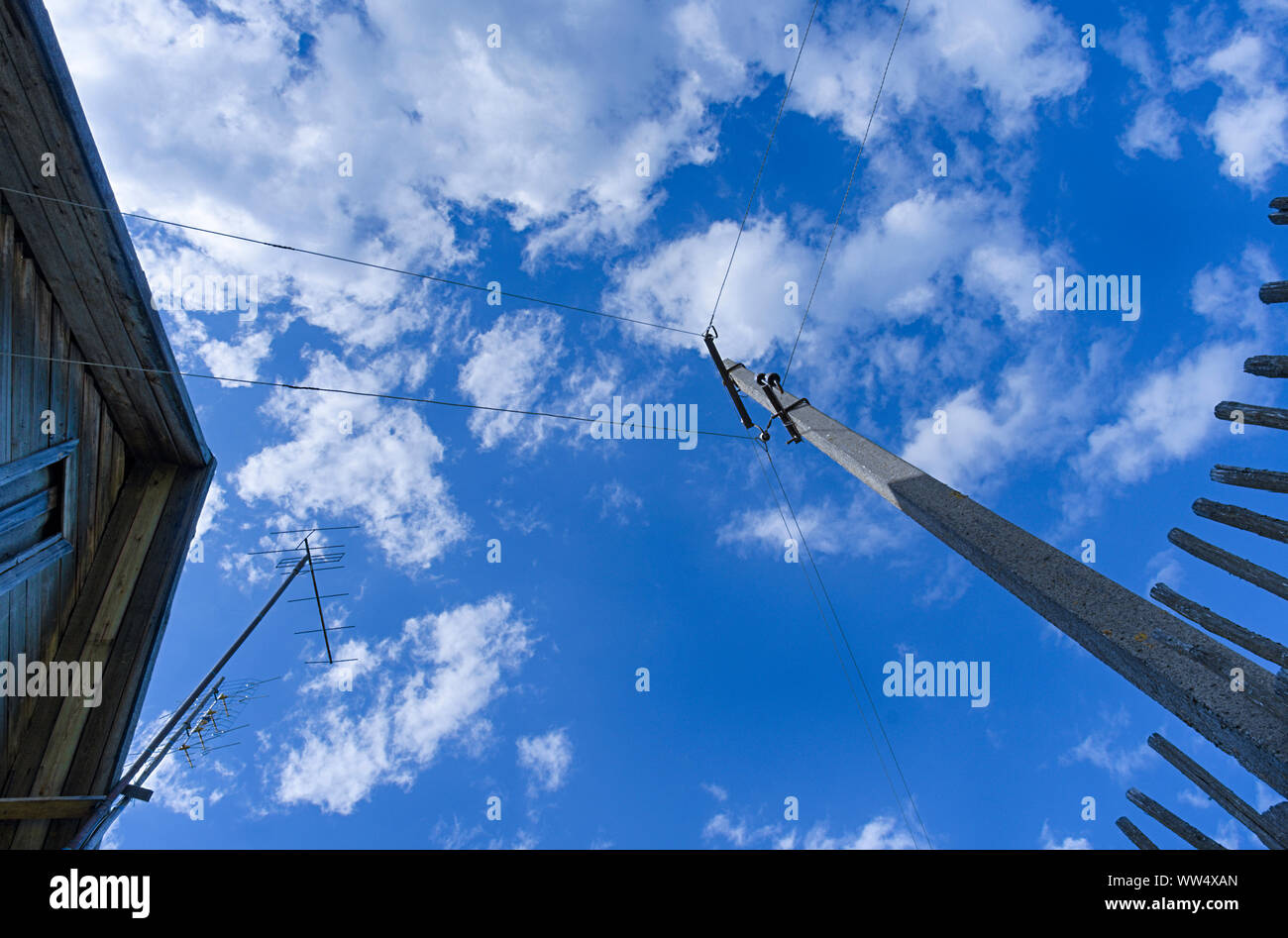 Concrete pole with electrical wires next to a wooden fence and part of the roof of a village house in the background of a blue sky with clouds Stock Photo