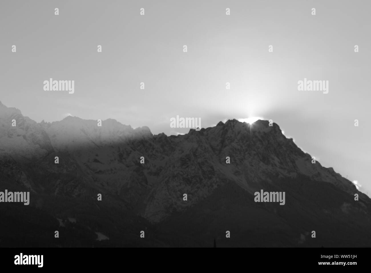 The wintry sun setting directly over Zugspitze, Stock Photo