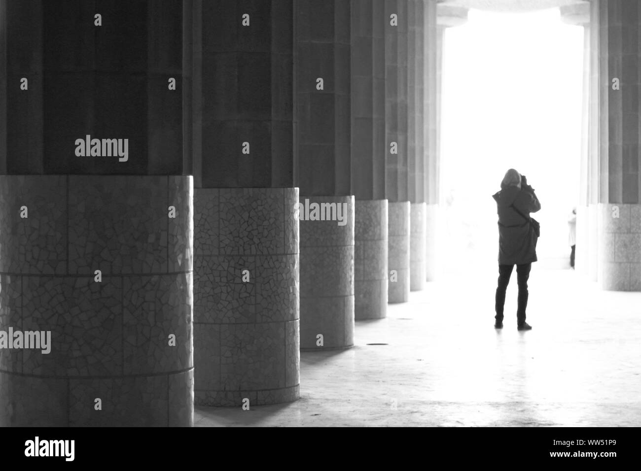 A person taking photos in the column court of the Park Guell, Stock Photo