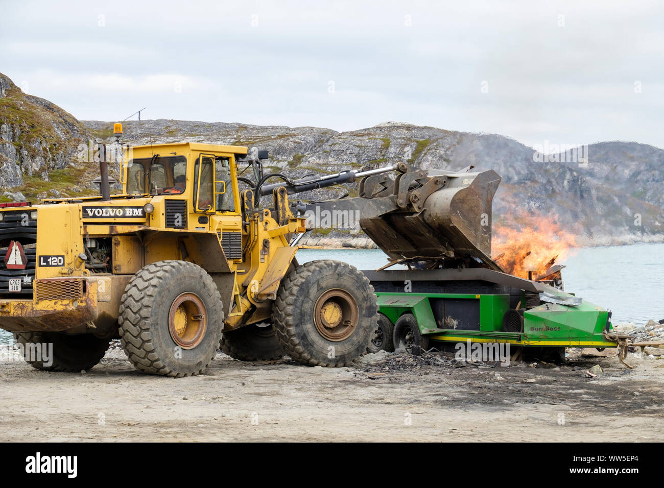 A digger dumping garbage into a BurnBoss burning rubbish at the local tip. Paamiut (Frederikshåb), Sermersooq, Greenland Stock Photo