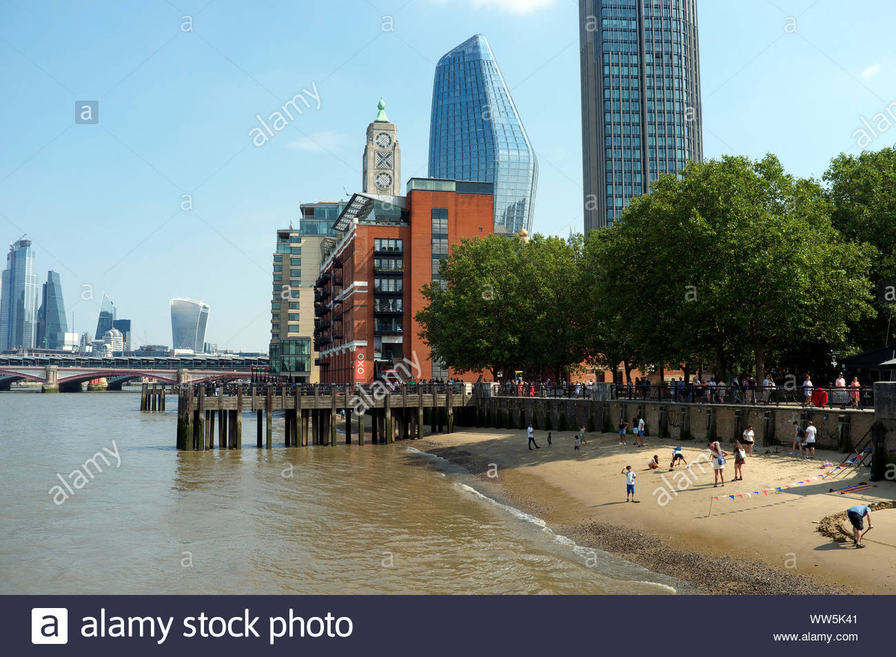 People enjoy the summer on a beach exposed by the River Thames in central London, UK. Stock Photo