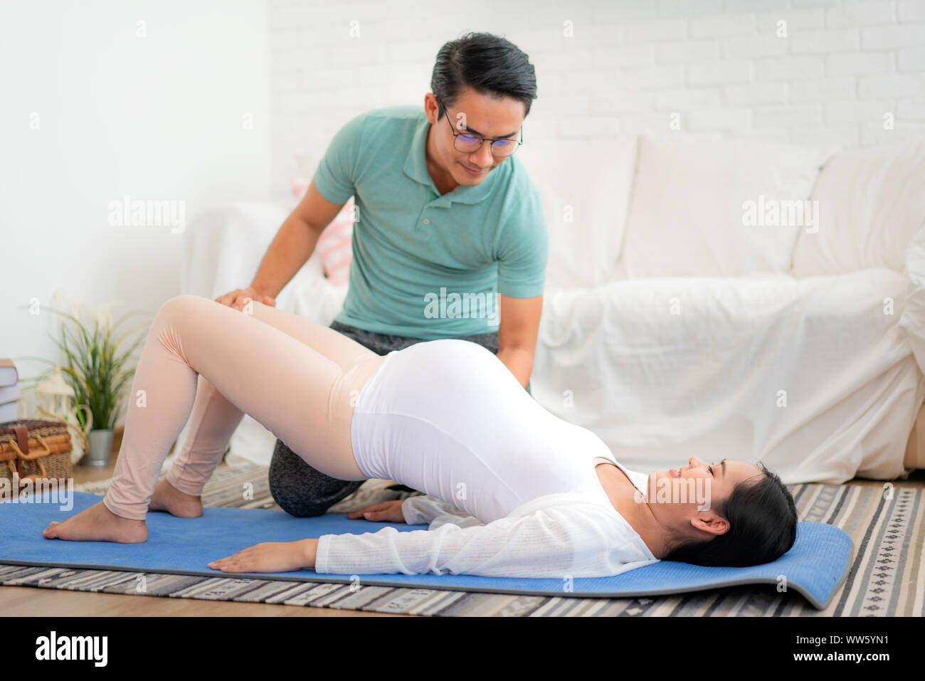 Asian young Husband help his wife exercise by yoga in living room at house. Happy family concept. Stock Photo
