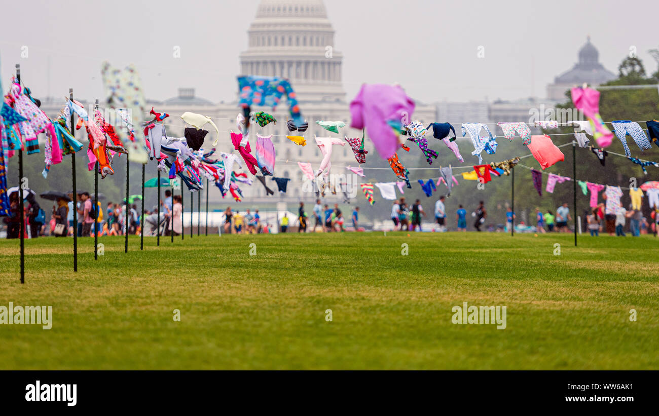 Washington DC, USA - June 9, 2019: Family Separation Protests. Symbolic washing cords with a small children's clothes next to the Capitol building. Stock Photo