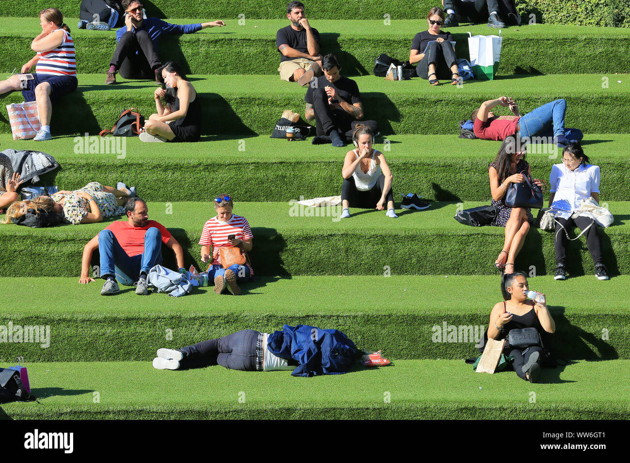 London, UK, 13th Sep 2019. An early autumn mini heat wave with warm sunshine brings out sunbathers by the Regent's Canal at Granary Square near King's Cross in London this afternoon. Credit: Imageplotter/Alamy Live News Stock Photo