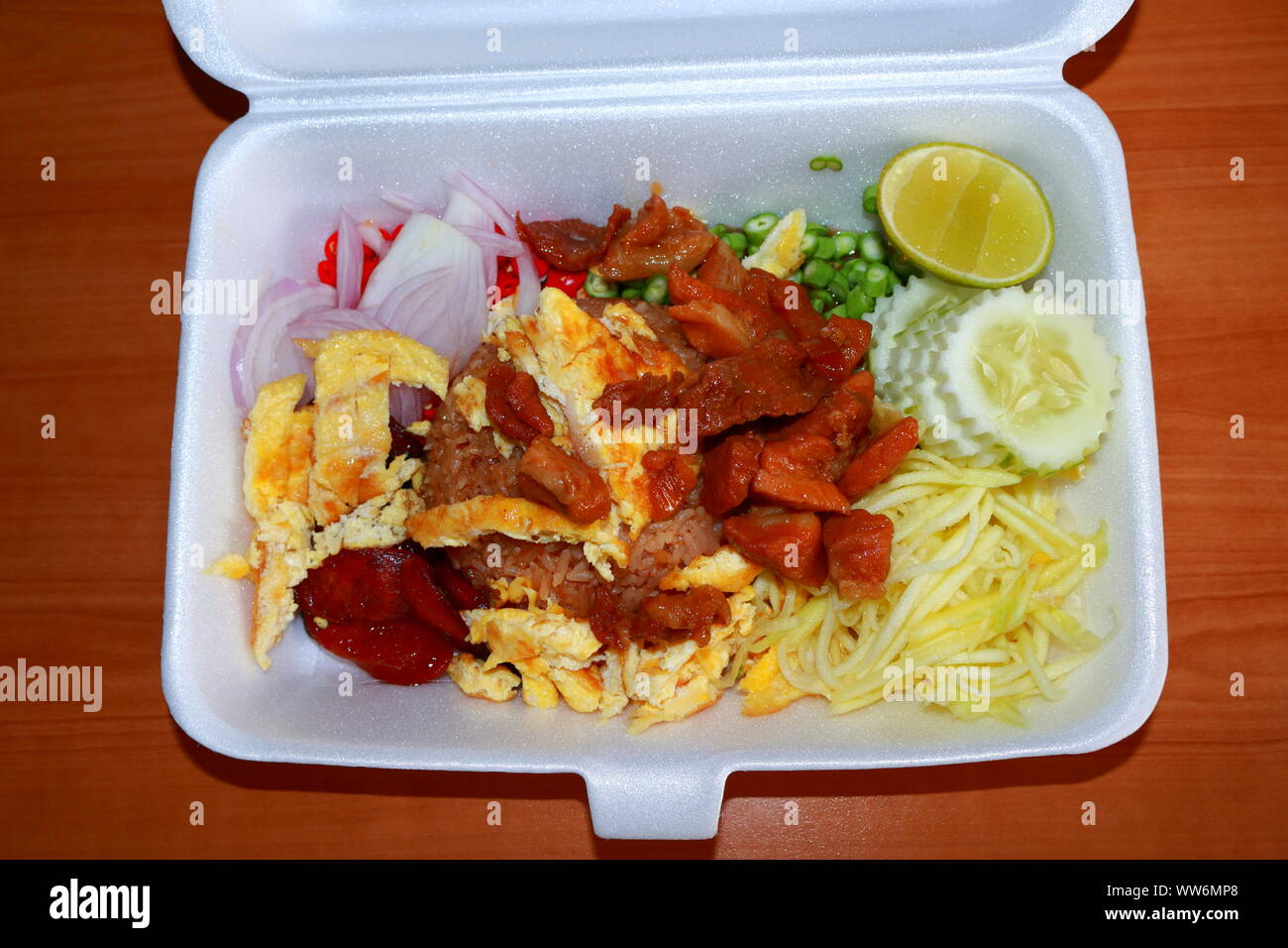 Fried rice mixed with shrimp paste, pork, sausage, egg, sliced mango and onion etc., street food in foam box. This is popular Thai food, it is called Stock Photo