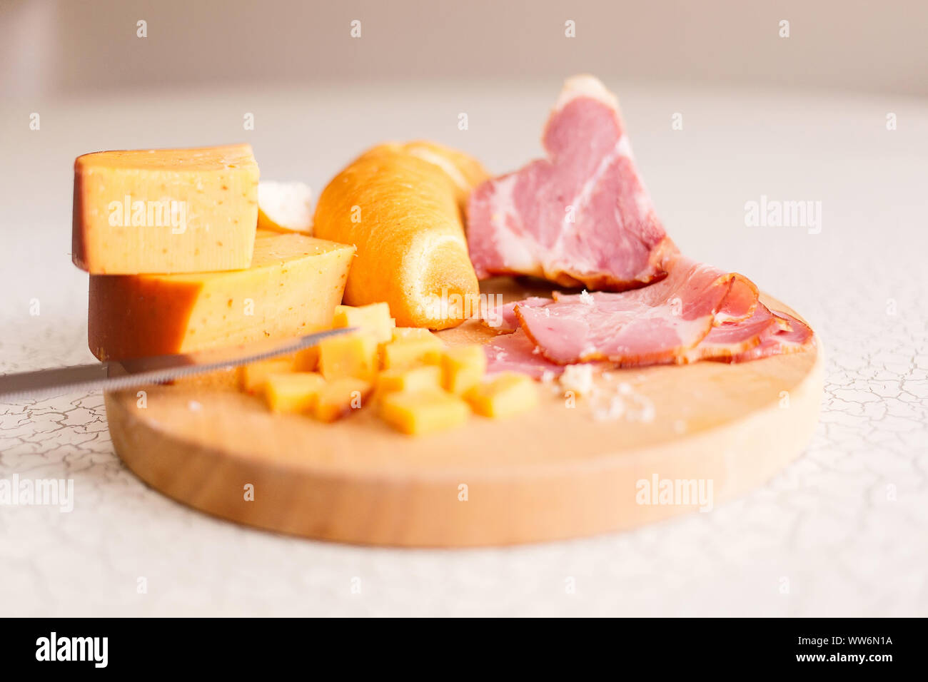 Ham, cheese and bread on a wooden cutting board. The breakfast in the village. Snack with beer or wine. Stock Photo