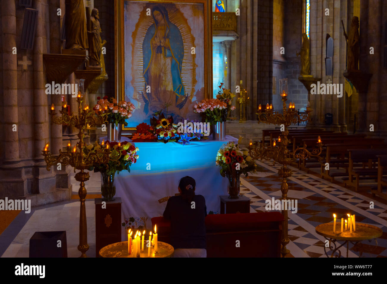 Quito, Pichincha, Ecuador. December 05 2017: Woman Praying in the Basilica of the National Vote. Due to its size and style, it is considered the large Stock Photo