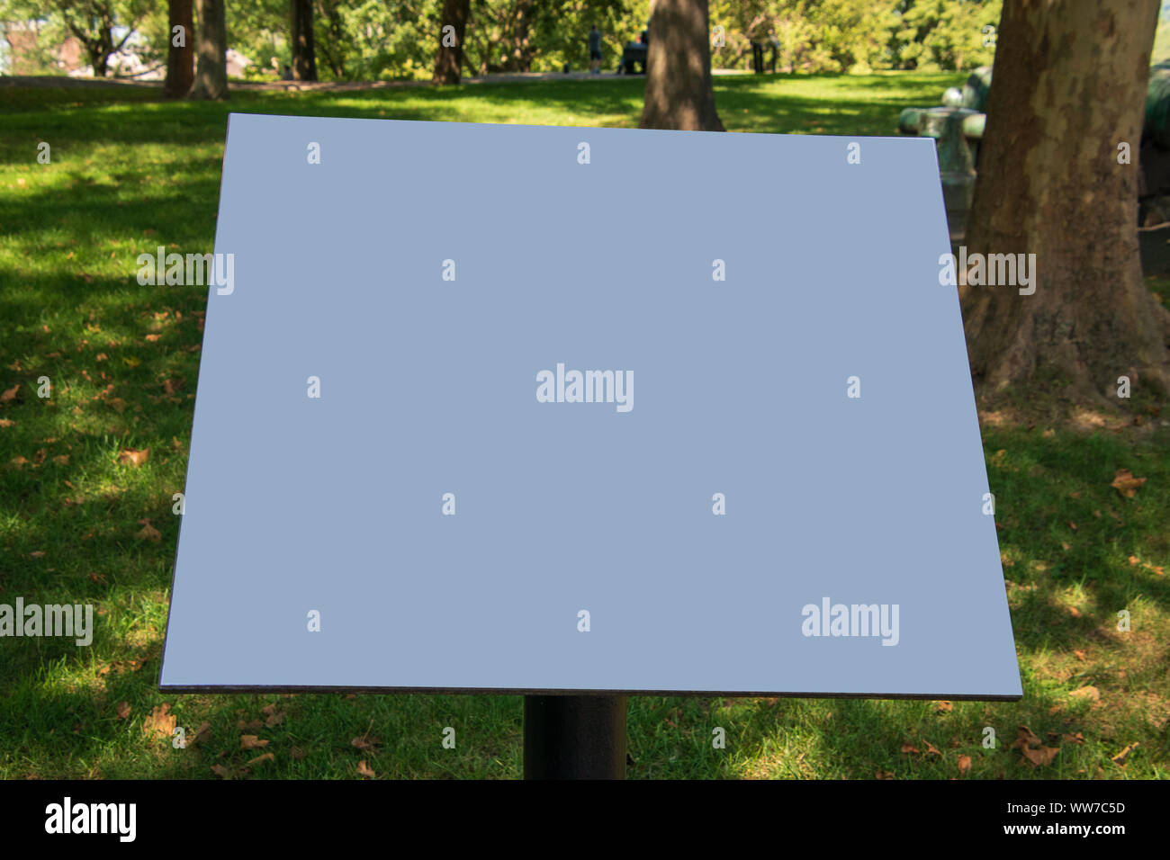 Blank blue sign on pedestal with a green grass and trees park like background Stock Photo