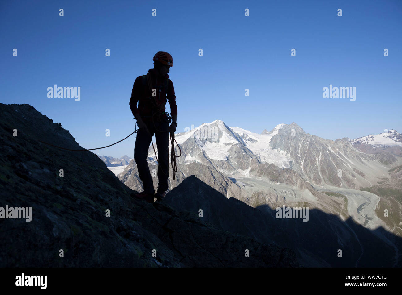 Climbing the summit of Dent de Tsalion over Arolla with views of Pigne d'Arolla and Mont Blanc de Cheilon, Val d'Hérens, Valais, Switzerland Stock Photo