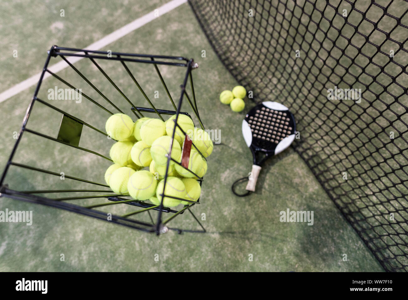 Paddle tennis objects on turf, balls, racket, net…focus on basket balls, Stock Photo