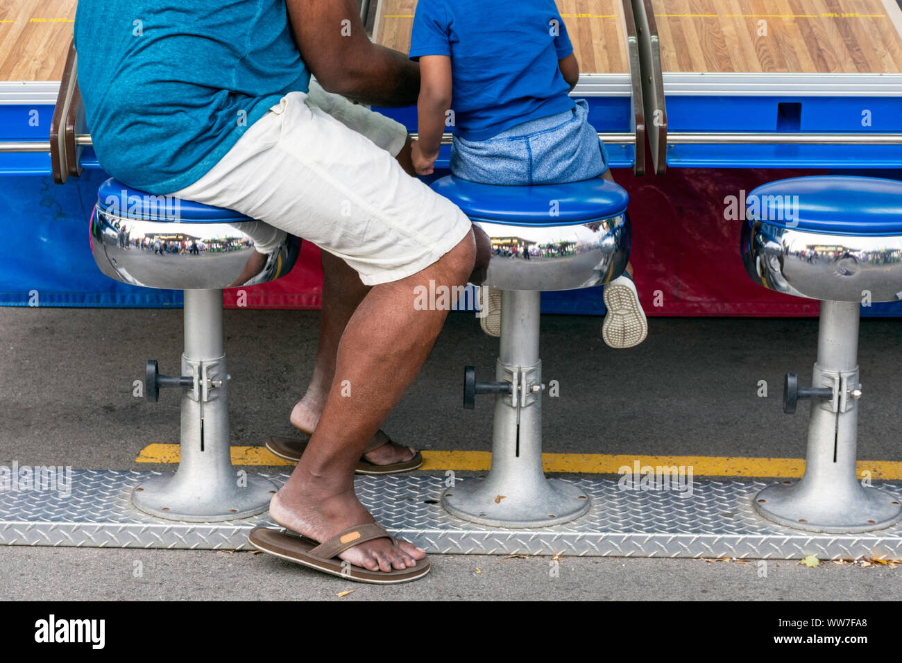 A young boy and his father enjoy playing a carnival midway game together, evoking the concepts of love, togetherness, and quality time. Stock Photo