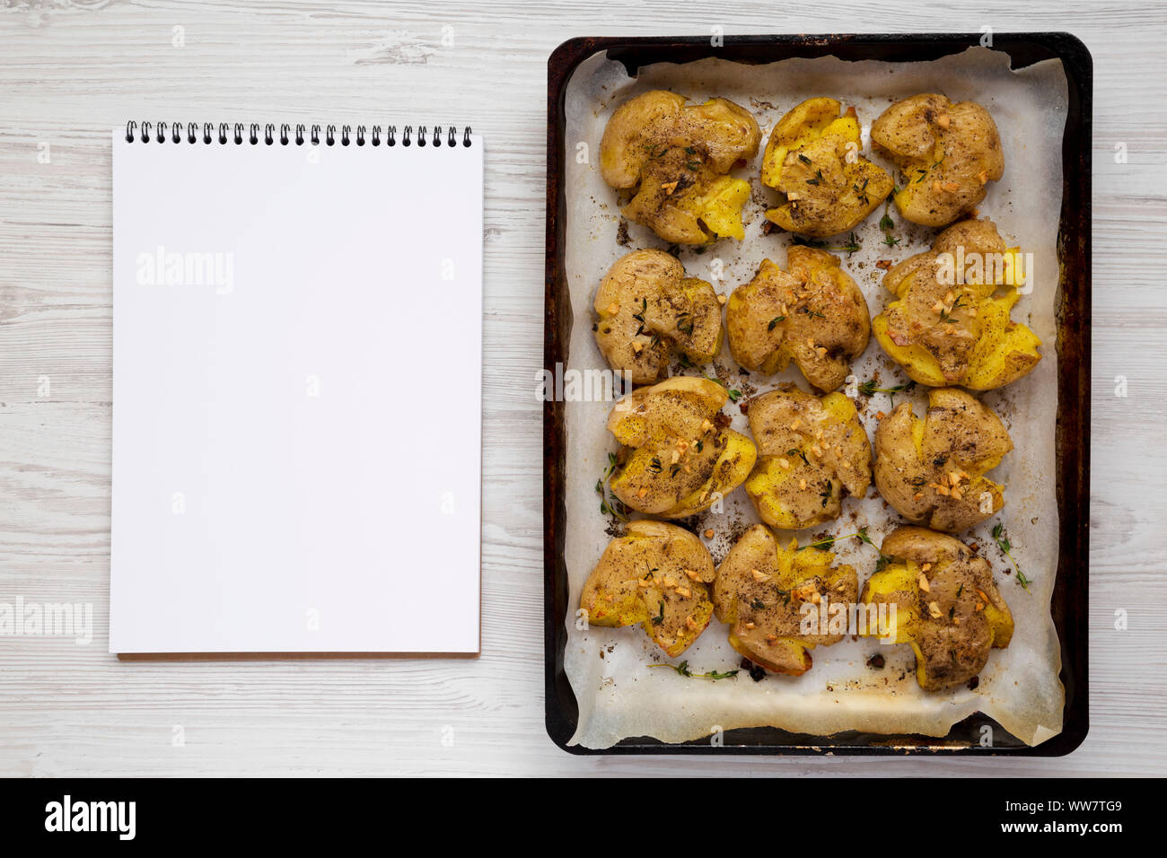 Overhead view, homemade garlic thyme smashed potatoes on a tray, blank notepad. Flat lay, overhead, from above. Copy space. Stock Photo