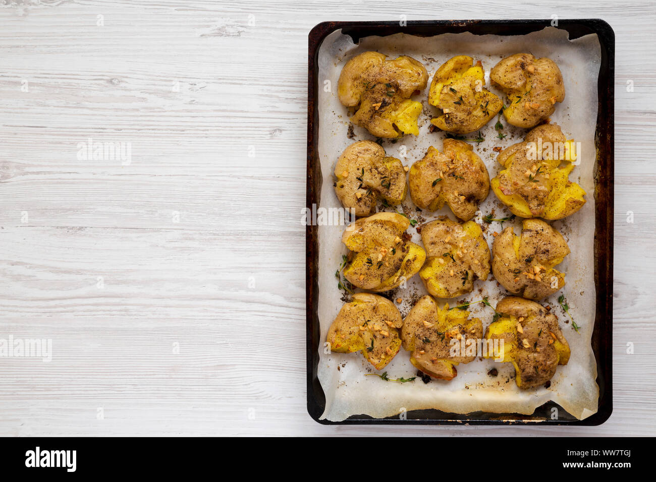 Homemade garlic thyme smashed potatoes on a tray, top view. Flat lay, overhead, from above. Copy space. Stock Photo