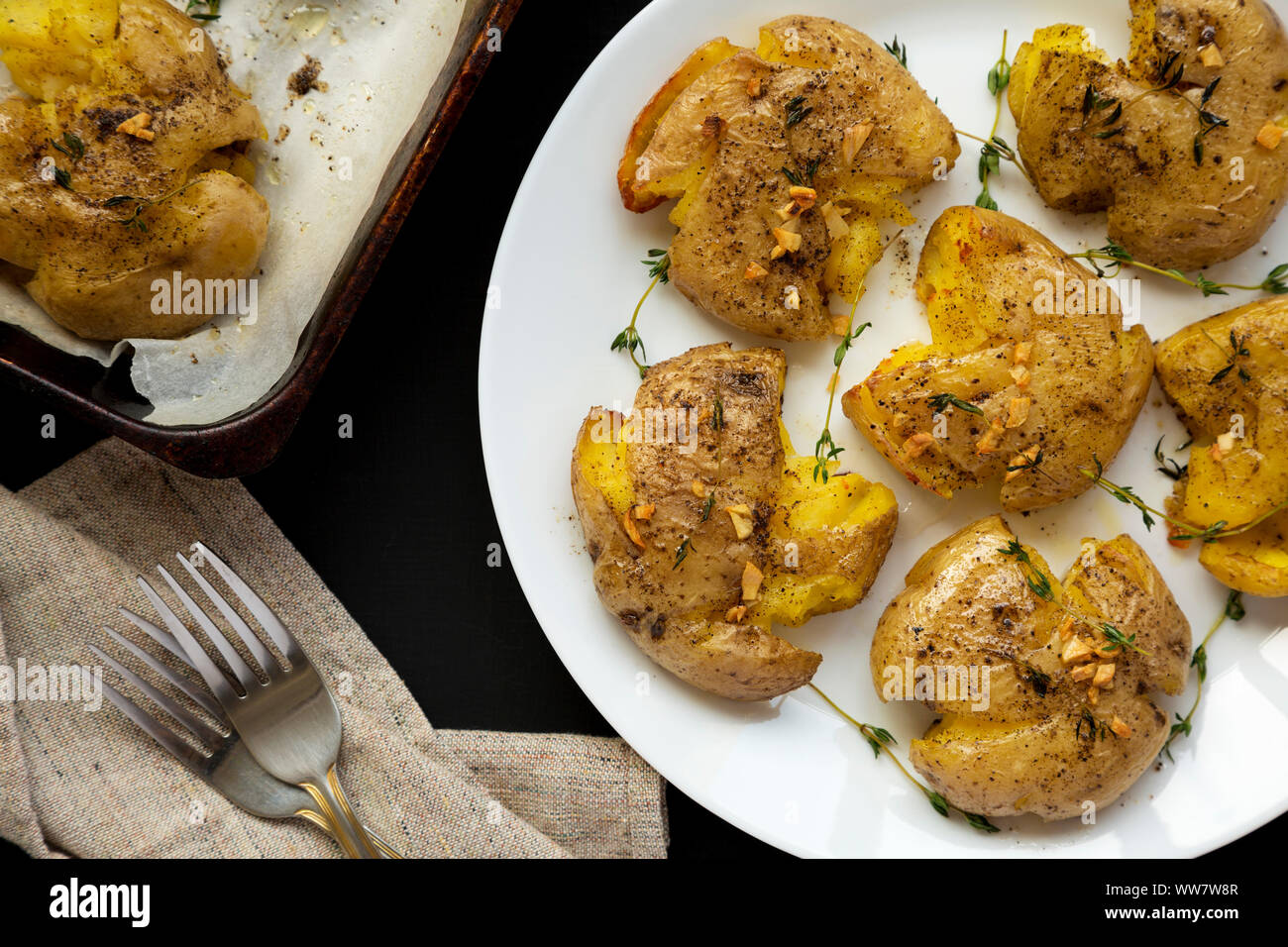 Homemade garlic thyme smashed potatoes on a white plate on a black background, top view. Flat lay, overhead, from above. Close-up. Stock Photo
