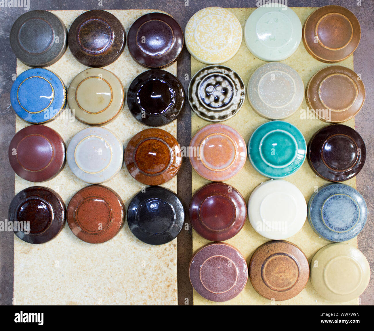 Several round clay samplers with multi-colored glazes on them lie on the square stones after firing. Stock Photo