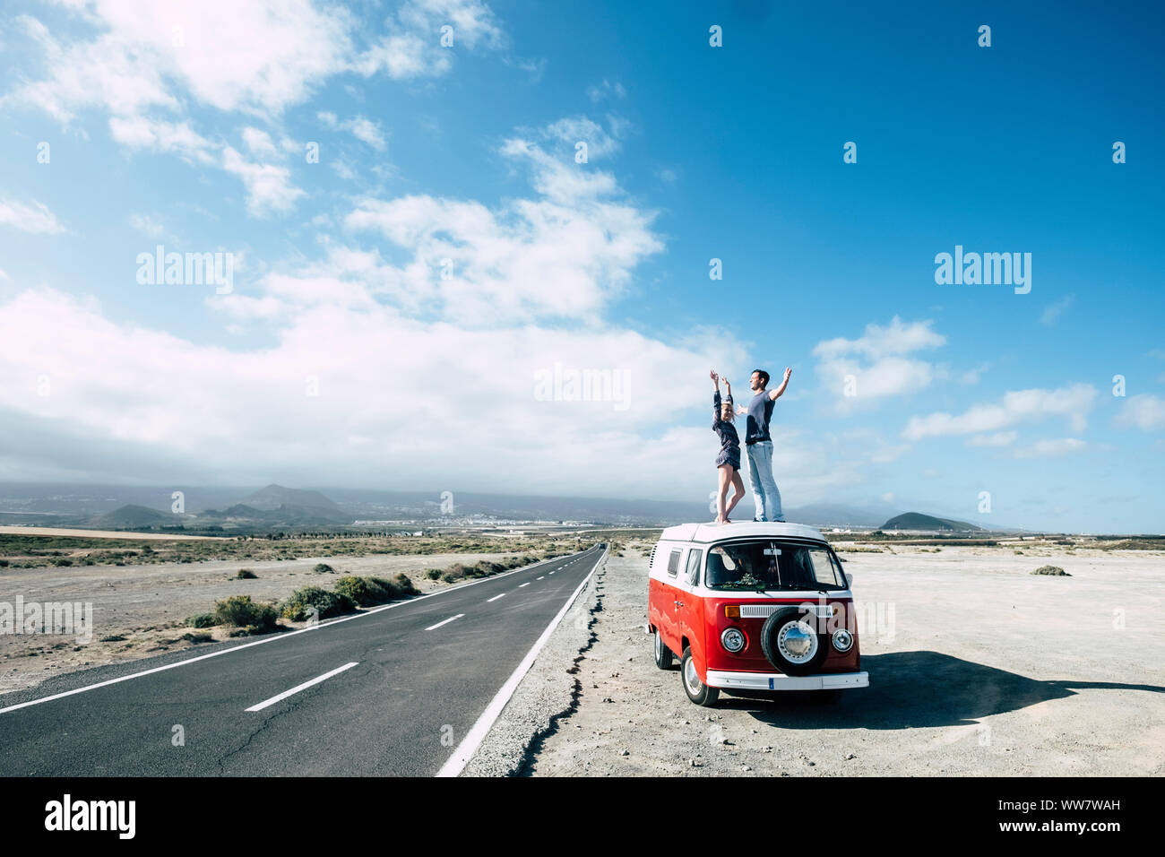 hippy style for an alternative vacation time outdoor leisure activity for young couple caucasian beautiful staying on the rooftop of a vintage van near a long road for travel concept. Stock Photo
