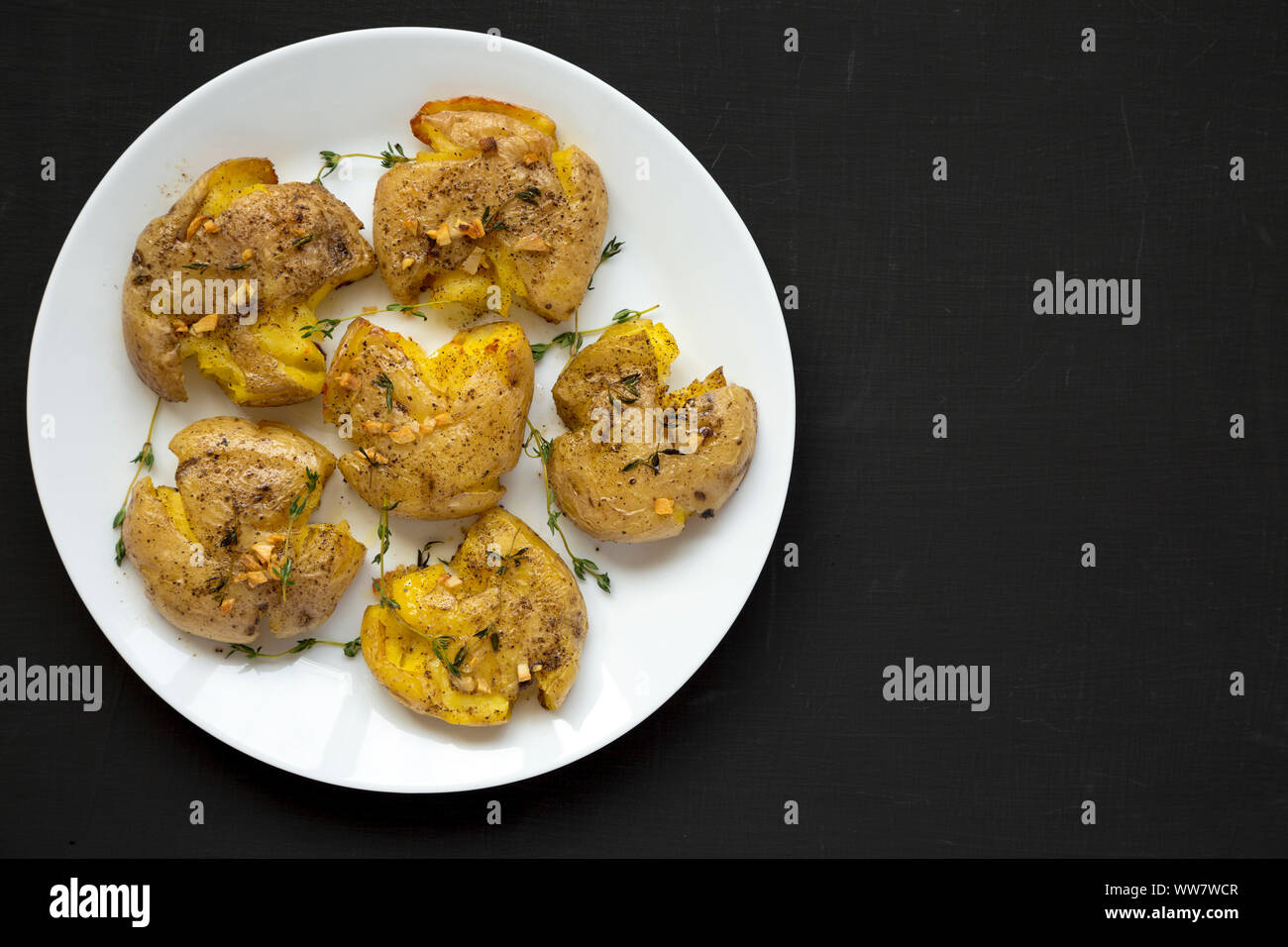 Homemade garlic thyme smashed potatoes on a white plate on a black background, top view. Flat lay, overhead, from above. Space for text. Stock Photo