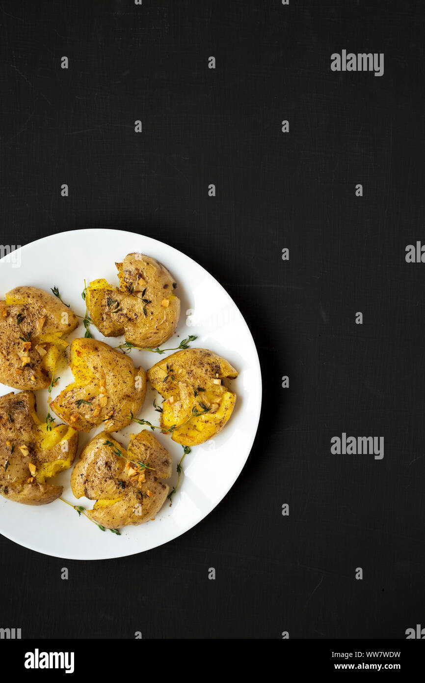 Homemade garlic thyme smashed potatoes on a white plate on a black surface, top view. Flat lay, overhead, from above. Copy space. Stock Photo