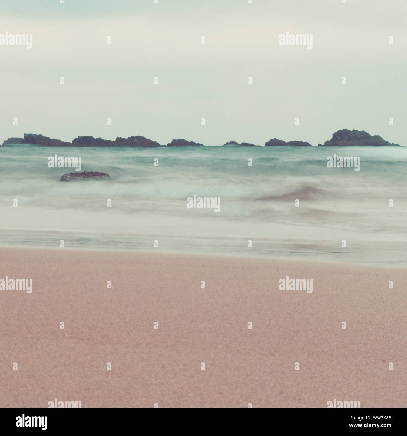 fine art ocean waves and rocks landscape in pastel tones. vintage colors. beach, waves and sky in same tones for artistic outdoor conceptual image Stock Photo