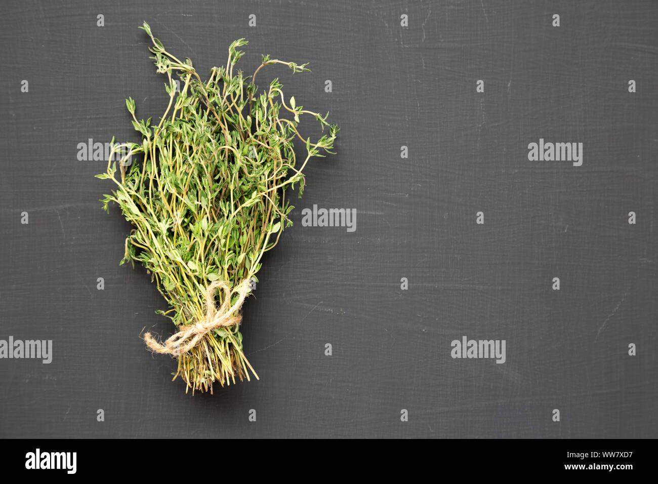 Raw organic fresh thyme on a black background, top view. Flat lay, overhead, from above. Copy space. Stock Photo
