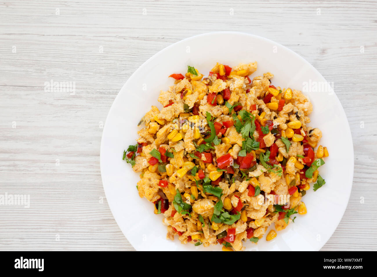 Homemade southwestern egg scramble on a white plate on a white wooden table. Flat lay, overhead, from above. Space for text. Stock Photo