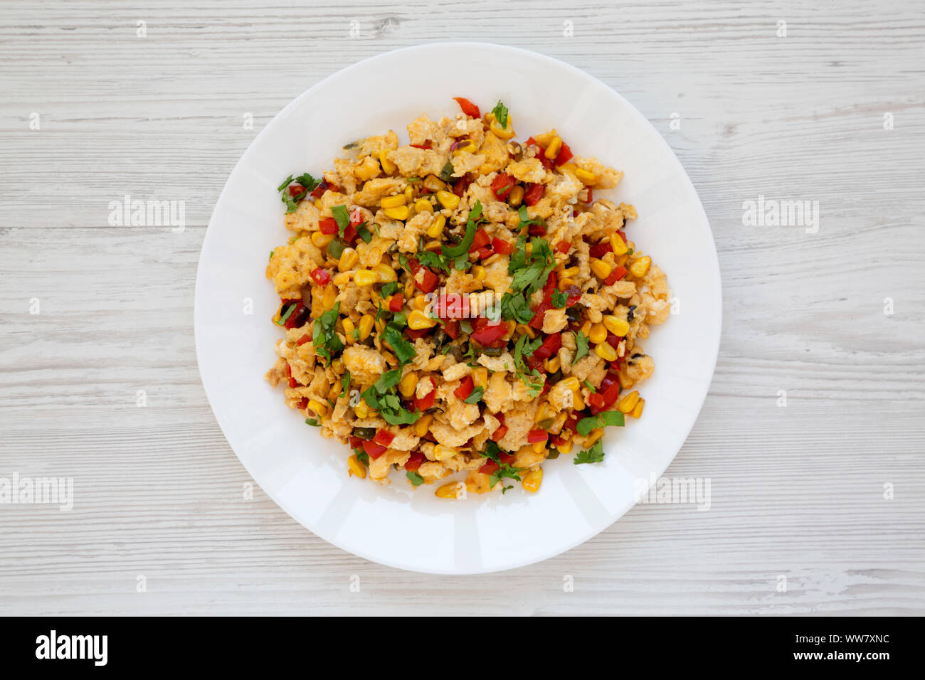 Homemade southwestern egg scramble on a white plate on a white wooden background, top view. Flat lay, overhead, from above. Stock Photo