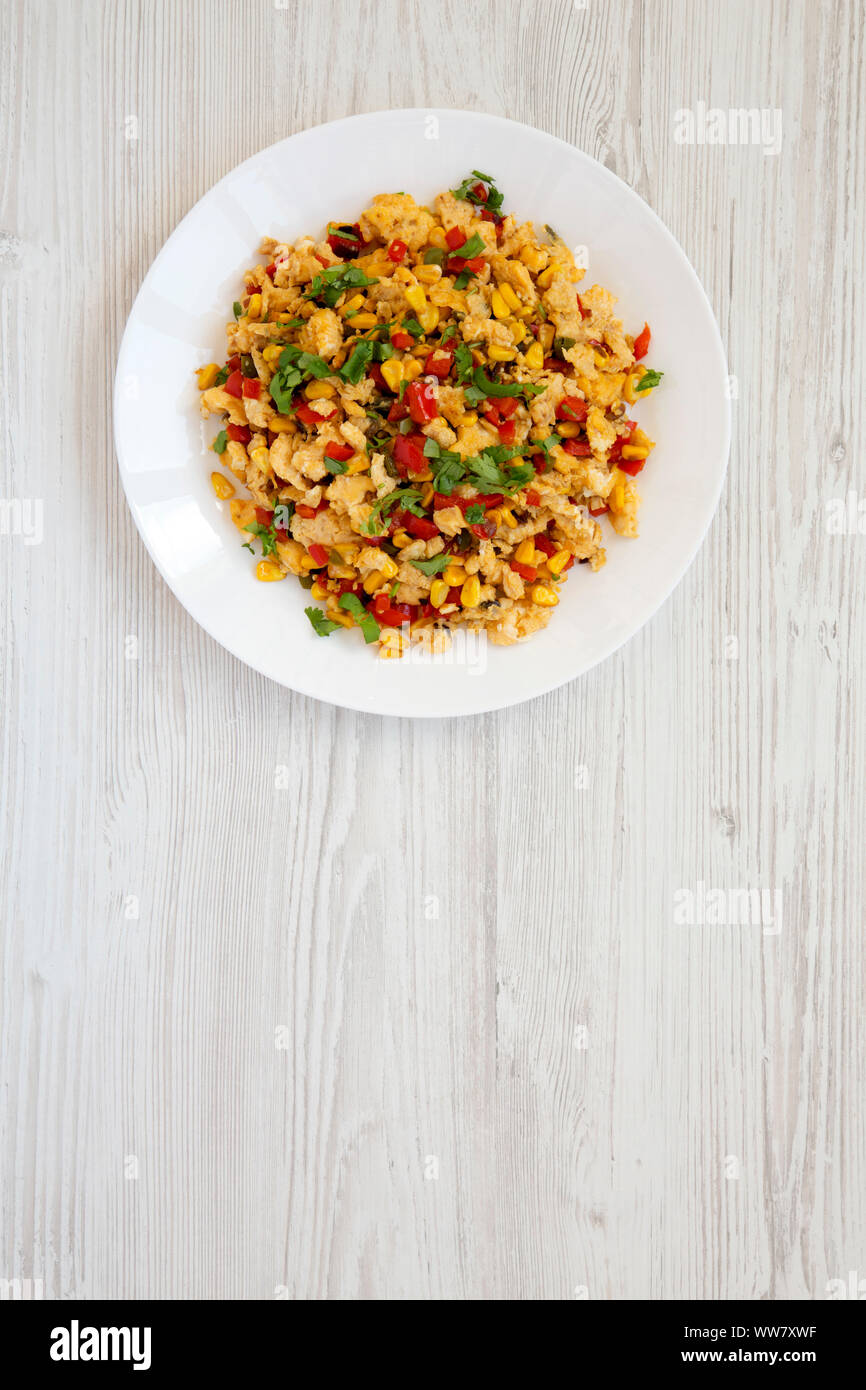 View from above, homemade southwestern egg scramble on a white plate on a white wooden background. Flat lay, top view, from above. Copy space. Stock Photo