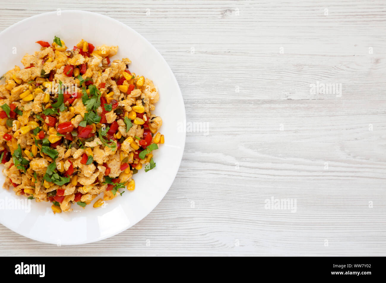 Homemade southwestern egg scramble on a white plate on a white wooden surface. Flat lay, top view, from above. Copy space. Stock Photo