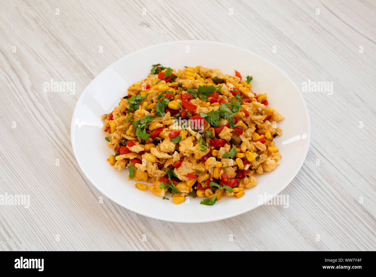 Homemade southwestern egg scramble on a white plate on a white wooden background, side view. Stock Photo
