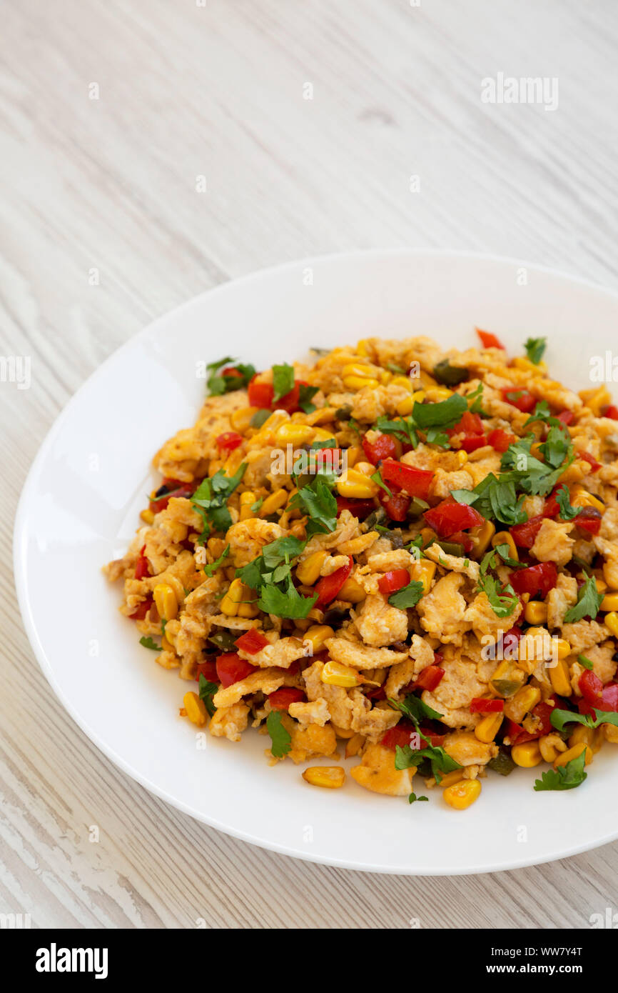 Homemade southwestern egg scramble on a white plate on a white wooden surface, side view. Copy space. Stock Photo