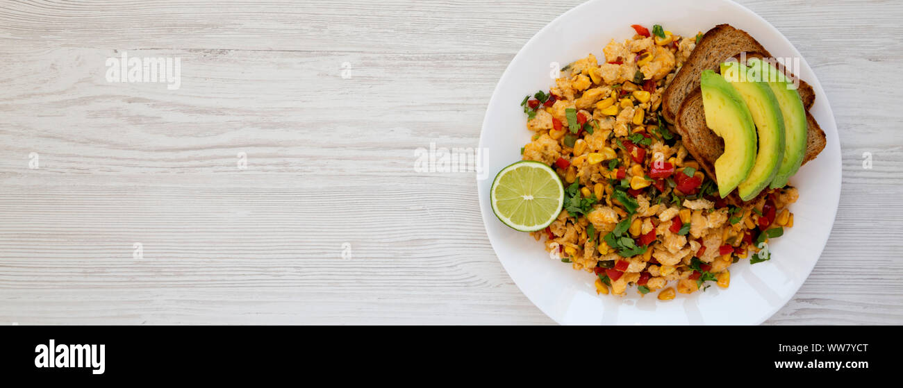 Homemade southwestern egg scramble with toast on a white plate on a white wooden surface. Flat lay, overhead, from above. Space for text. Stock Photo
