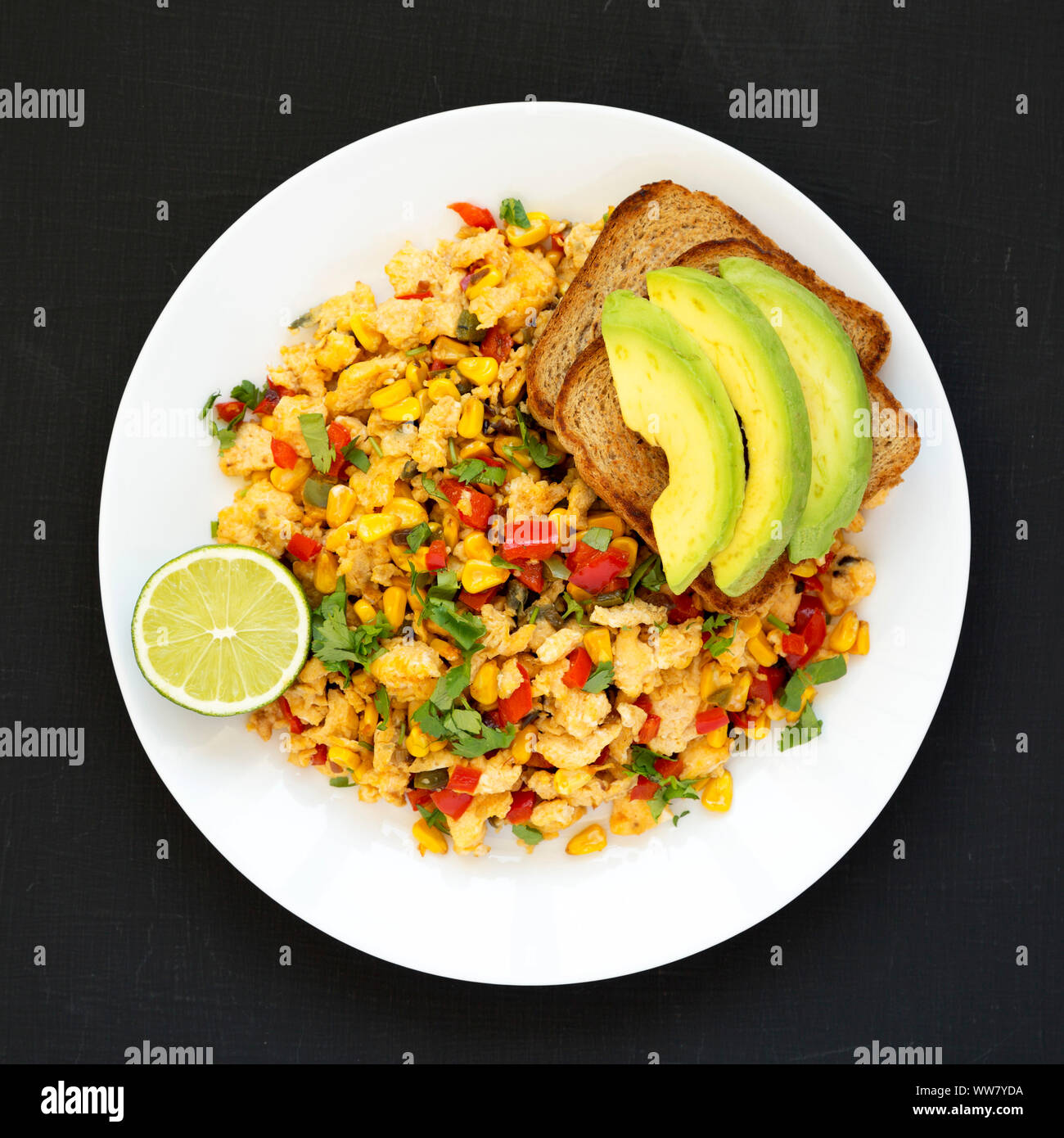 Overhead view, homemade southwestern egg scramble with toast on a white plate over black surface. Flat lay, top view, from above. Close-up. Stock Photo