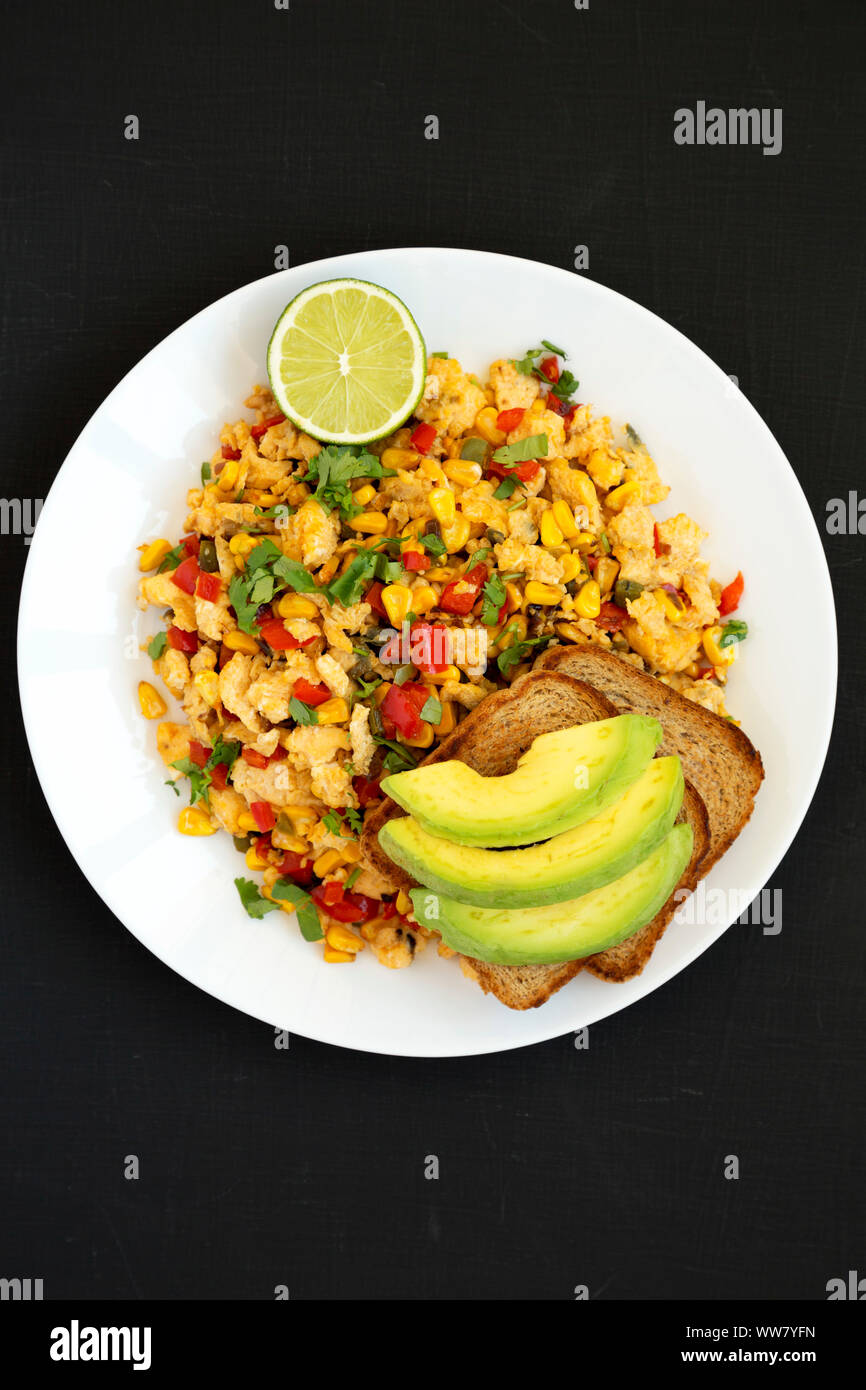 Homemade southwestern egg scramble with toast on a white plate on a black background, overhead view. Flat lay, top view, from above. Close-up. Stock Photo