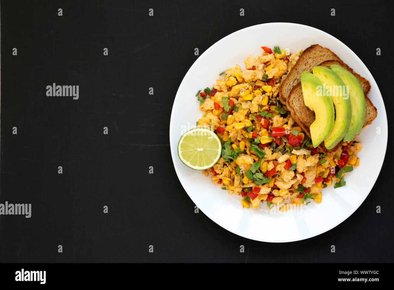 Homemade southwestern egg scramble with toast on a white plate on a black surface, top view. Flat lay, overhead, from above. Copy space. Stock Photo