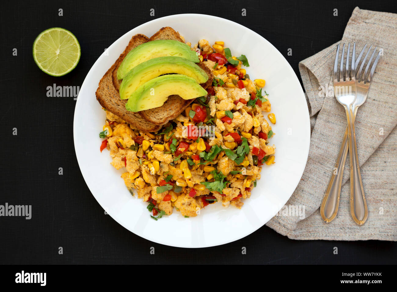Homemade southwestern egg scramble with toast on a white plate on a black surface, top view. Flat lay, overhead, from above. Close-up. Stock Photo