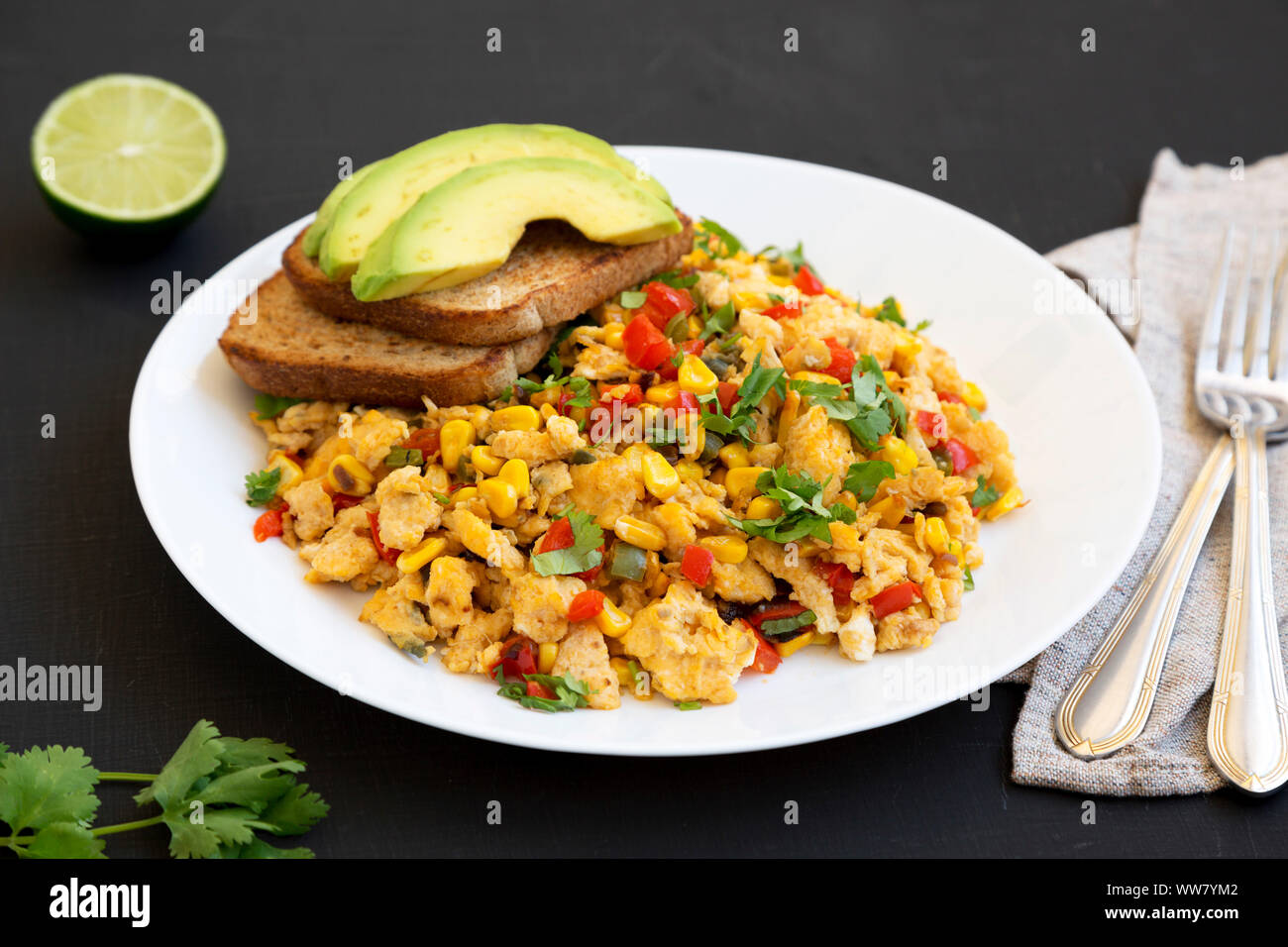 Homemade southwestern egg scramble with toast on a white plate on a black background, low angle view. Close-up. Stock Photo