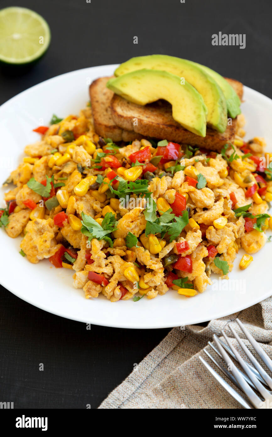 Homemade southwestern egg scramble with toast on a white plate on a black surface, side view. Close-up. Stock Photo