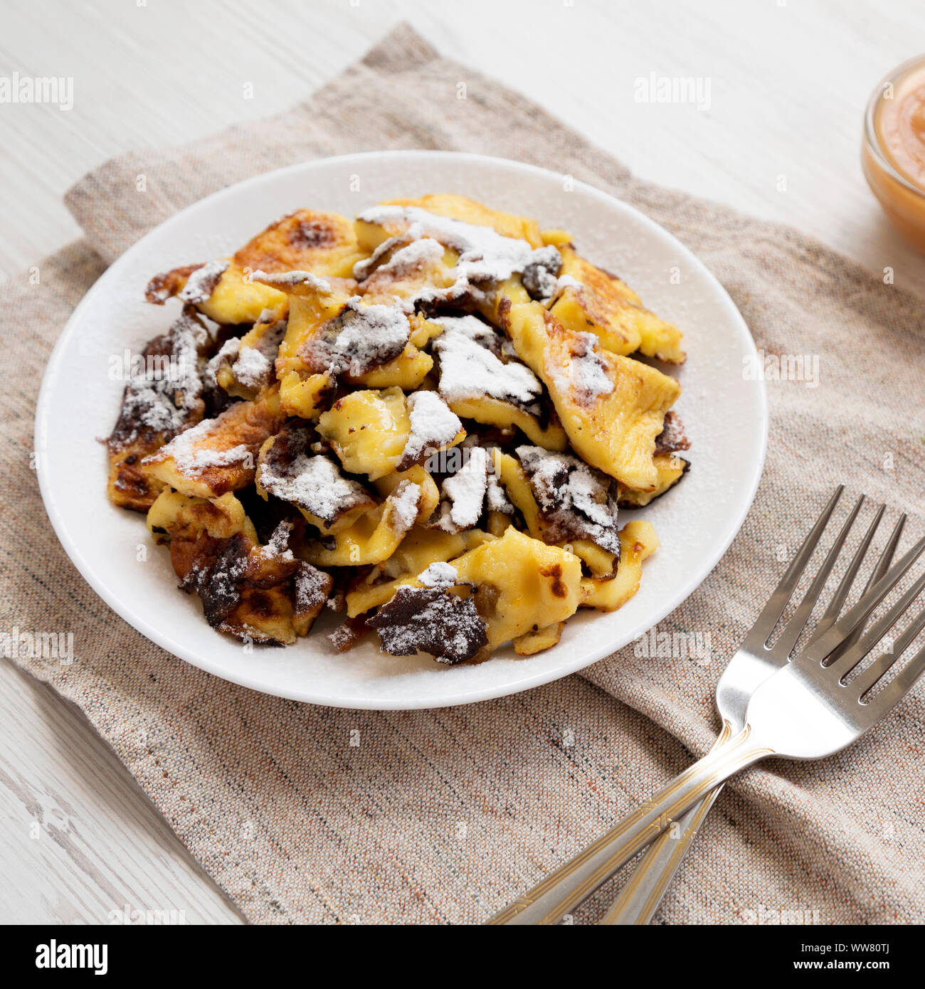 Homemade german Kaiserschmarrn pancake on a white plate, low angle view. Close-up. Stock Photo