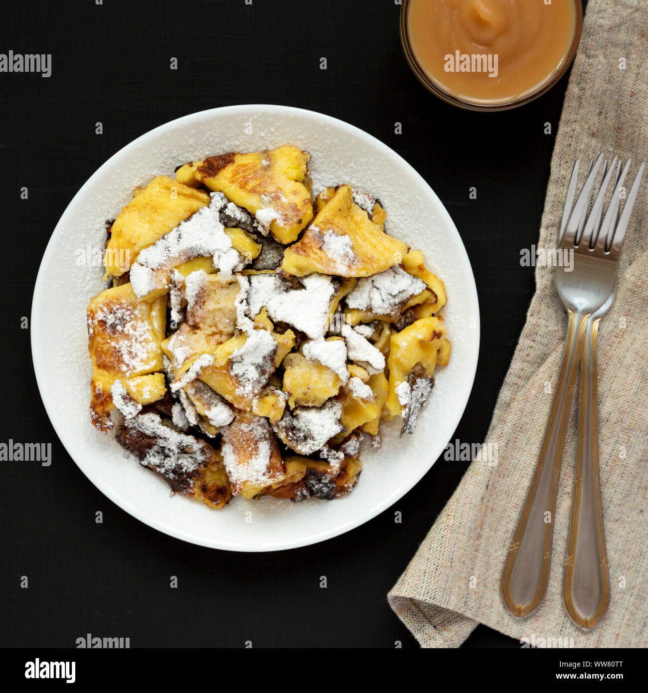 Top view, homemade german Kaiserschmarrn pancake with apple sauce on a black surface. Flat lay, overhead, from above. Close-up. Stock Photo