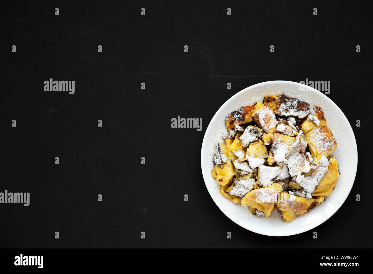 Homemade german Kaiserschmarrn pancake on a black surface, top view. Flat lay, overhead, from above. Copy space. Stock Photo