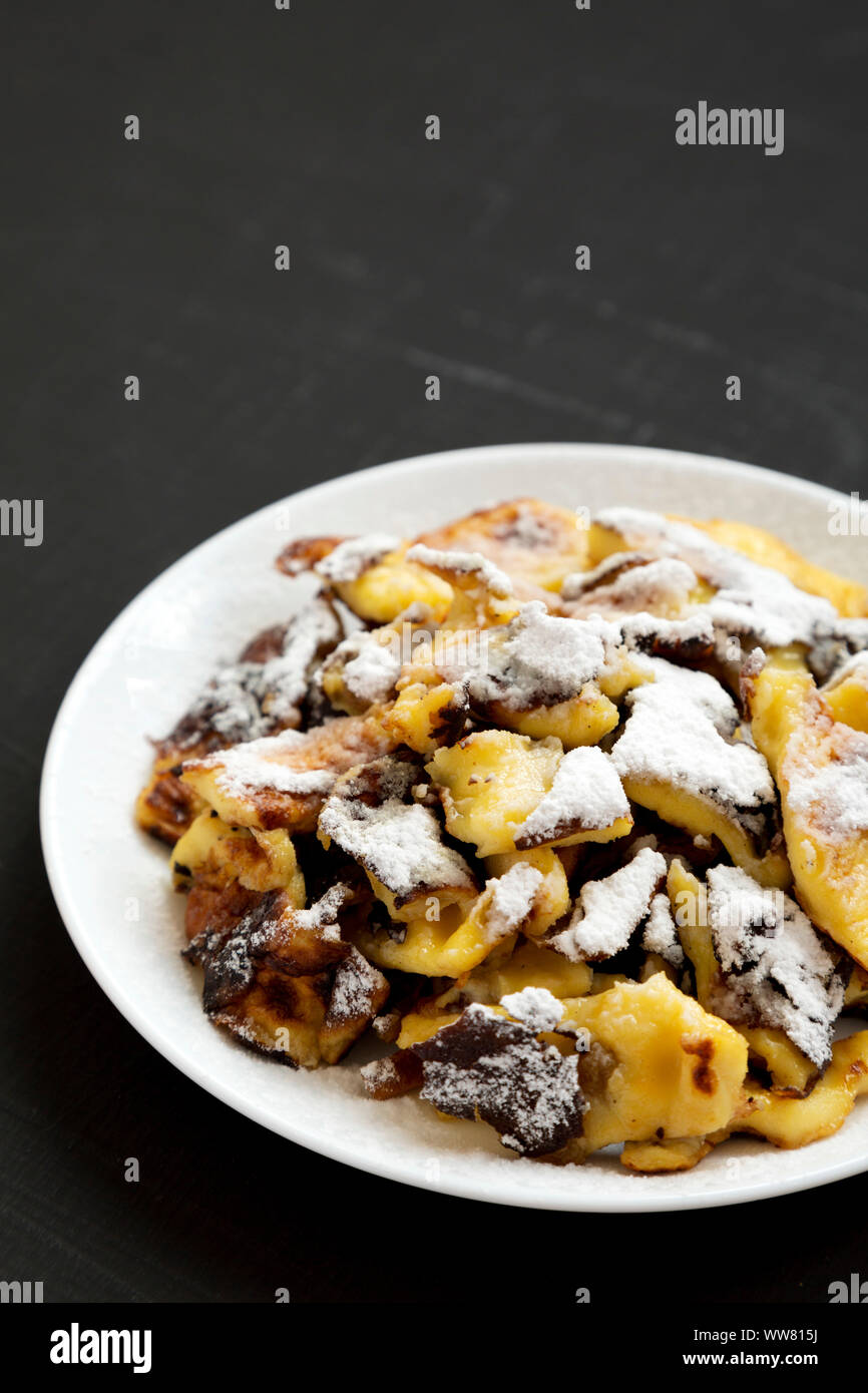 Homemade german Kaiserschmarrn pancake on a black background, side view. Copy space. Stock Photo
