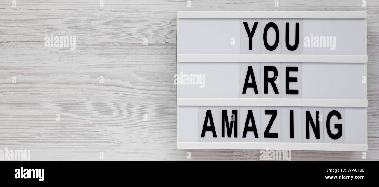 'You are amazing' words on a modern board on a white wooden surface, top view. Overhead, from above. Flat lay. Copy space. Stock Photo