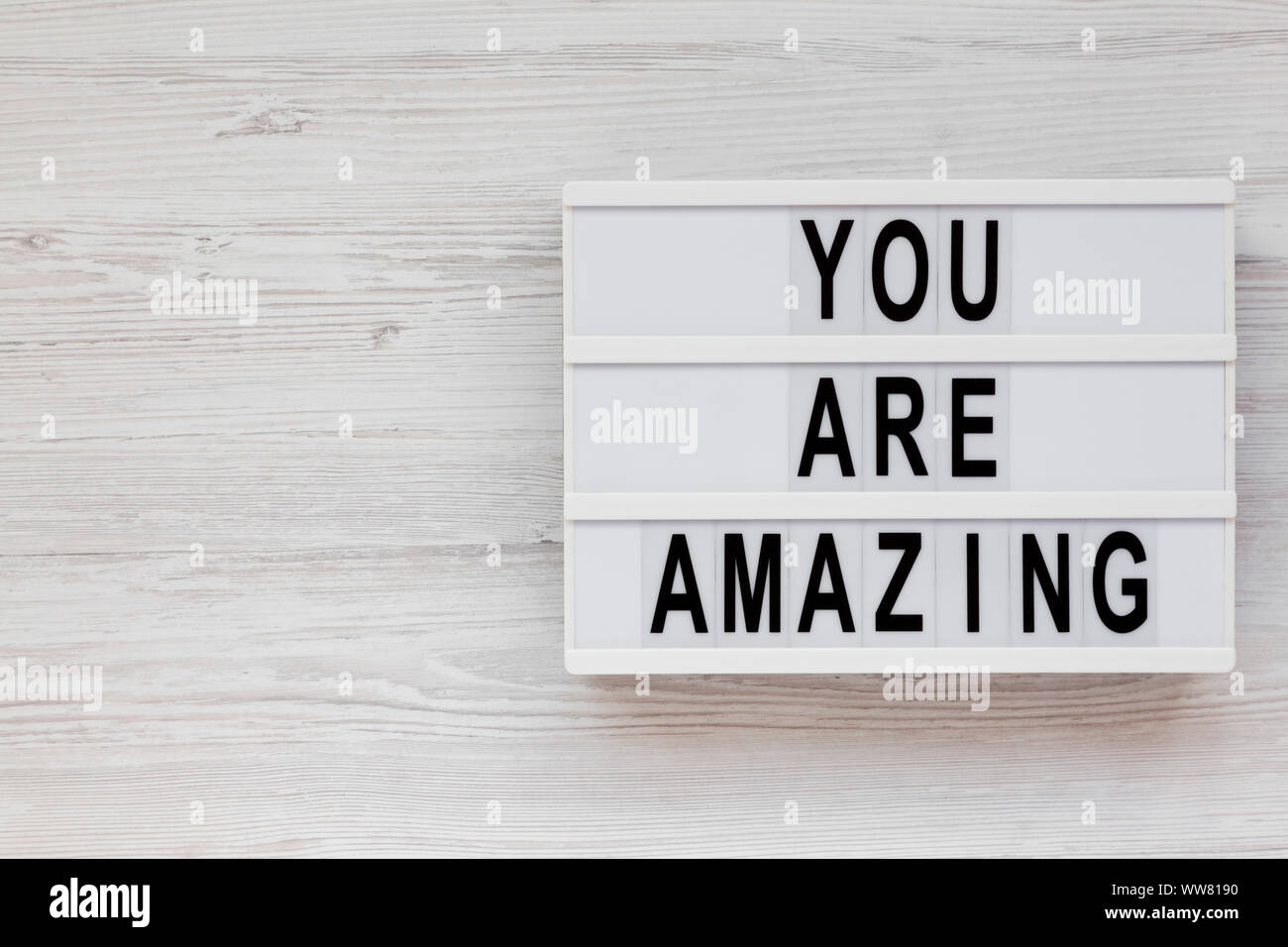 'You are amazing' words on a modern board on a white wooden background, top view. Overhead, from above. Flat lay. Space for text. Stock Photo