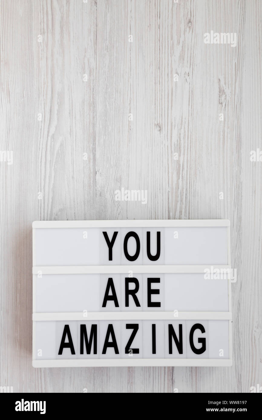 'You are amazing' words on a modern board on a white wooden background, overhead view. Top view, from above. Flat lay. Copy space. Stock Photo