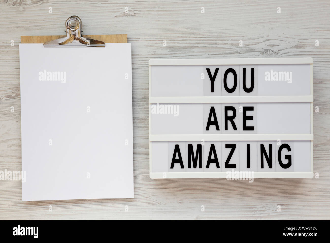 'You are amazing' words on a modern board, clipboard with blank sheet of paper on a white wooden background, overhead view. Top view, from above. Flat Stock Photo