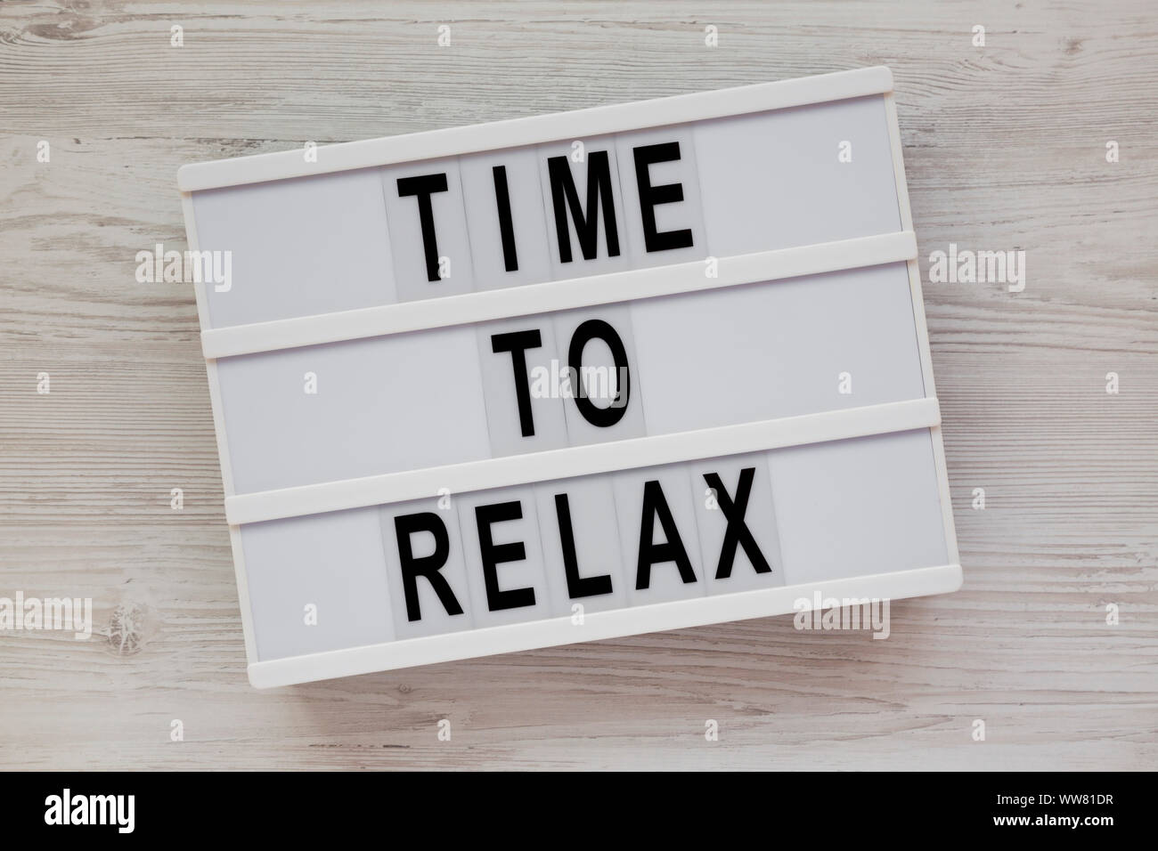 'Time to relax' words on a lightbox over white wooden surface, top view. Overhead, from above. Flat lay. Stock Photo