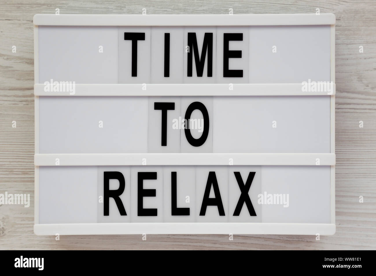 'Time to relax' words on a modern board over white wooden background, top view. Overhead, from above. Flat lay. Close-up. Stock Photo