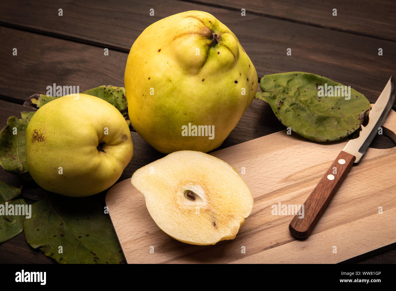 Fresh Quince fruit on wooden table. Cydonia oblonga Stock Photo